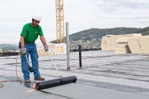 Ein Mitarbeiter der Boehi + Wirz AG verlegt eine Bitumenbahn auf einem Flachdach.