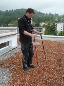 Ein Mitarbeiter von Böhi + Wirz überprüft ein Flachdach auf Lecks. Leckortung spart Kosten.