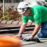 Ein Mitarbeiter der Boehi + Wirz AG verlegt Bitumenbahnen auf einem Flachdach.