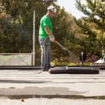 Ein Mitarbeiter der Boehi + Wirz AG dichtet ein Flachdach mit Bitumenbahnen ab.
