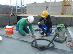 Zwei Mitarbeiter der Firma Boehi + Wirz befestigen während dem Neubau eines Flachdachs eine Absturzsicherung.