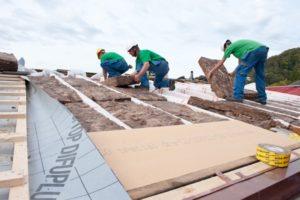 Drei Mitarbeiter der Firma Boehi + Wirz AG isolieren gemeinsam ein Steildach.