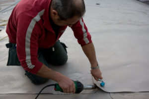 Ein Mitarbeiter der Boehi + Wirz AG verlegt eine Kunststoffabdichtung auf einem Flachdach.